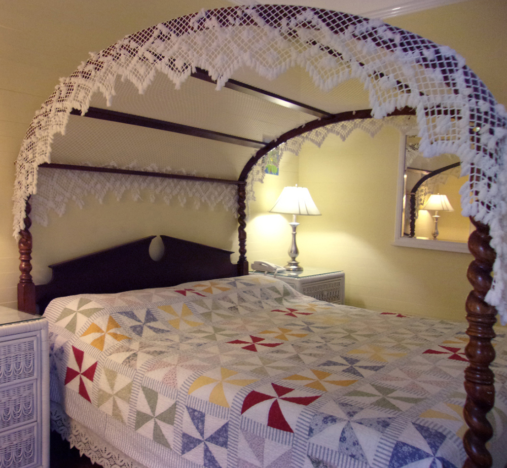 Canopy bed in Curry Mansion room. Opens in a photo gallery pop out.