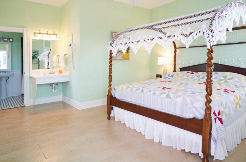 Our Accessibility room is located on the first floor of the Guest Wing adjacent to the wheelchair lift. A ramped entrance to the spacious King Balcony room that features our signature canopy bed with crocheted topper and hand-made quilt; a roll-up mirrored vanity and roll-in bathroom are portrayed in this photo.